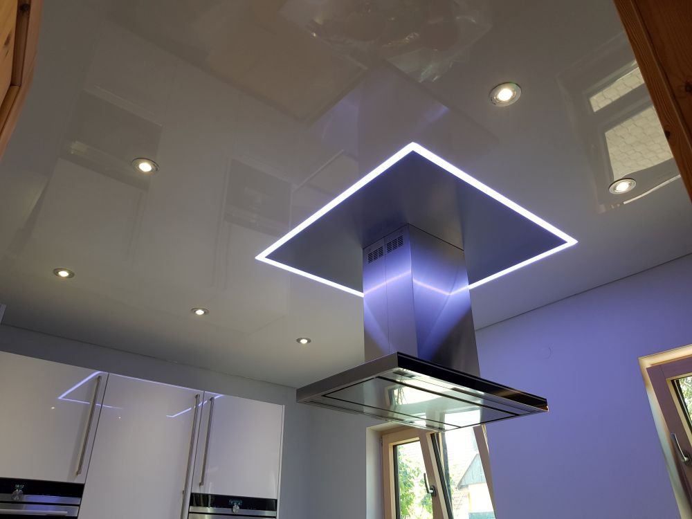Eine Kombination aus Lackspanndecke und Satinspanndecke mit einem leuchtendem Trennprofil und einer integrierten Dunstabzugshaube