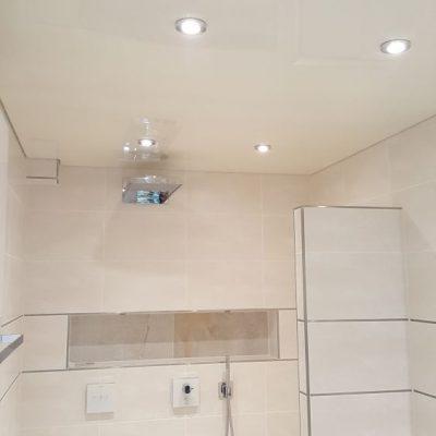 Eine weisse Lackspanndeckeim Bad mit Beleuchtung