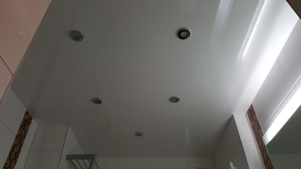Eine weiße Lackspanndecke im Bad mit speziellen spritzgeschützte Lampen